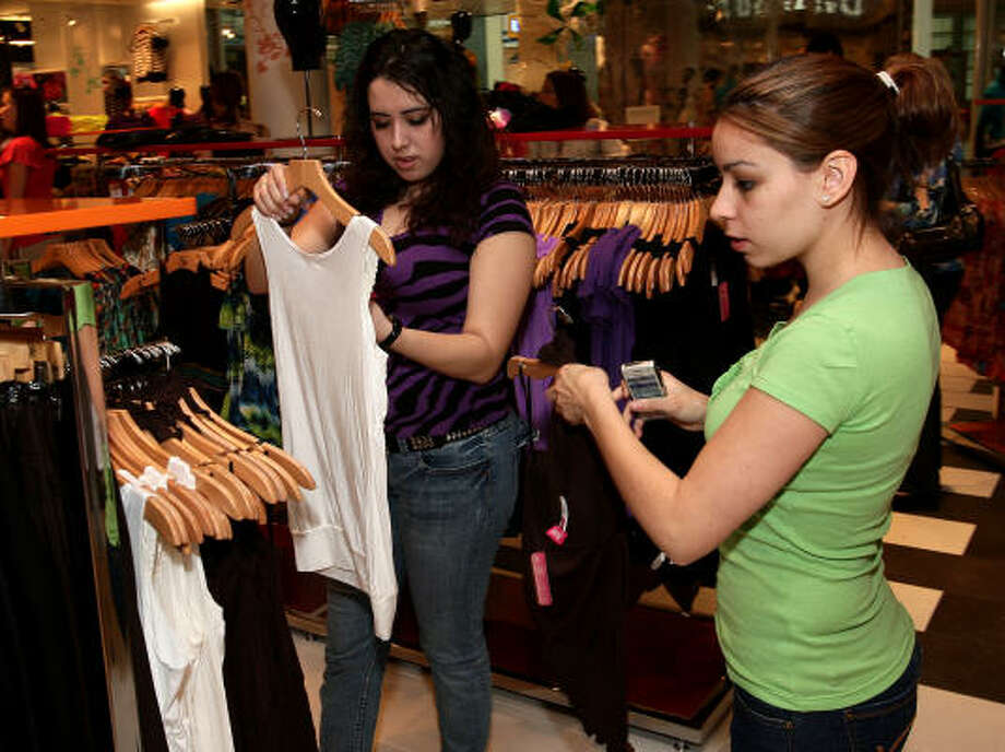 Vanessa Rangel, left, and Stephanie Zapata, two 20-year-olds from Missouri City, look over the merchandise at the grand opening in Sugar Land of Shasa, a clothing chain based in Mexico. Photo: Bob Levey :, For The Chronicle