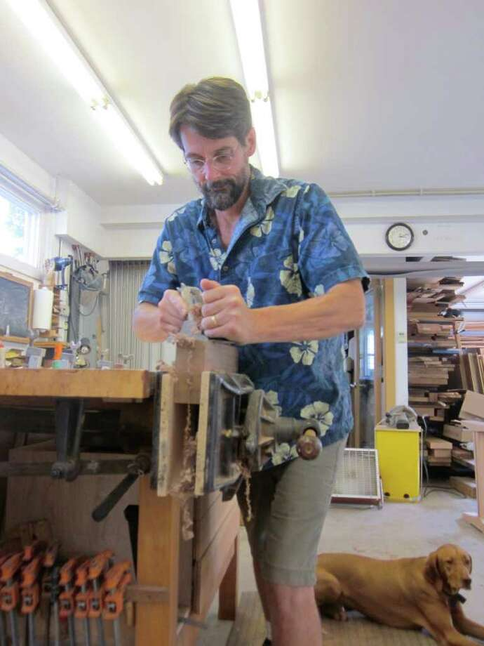 Tom Throop, owner of Black Creek Designs in New Canaan, planes a piece of wood at his Grove Street workshop. - Photo by john H. Palmer Photo: File Photo