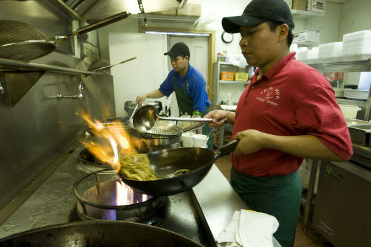 Pedro Sajbin, right, and his brother, Eliezer, prepare dishes of Chinese food using halal meat.