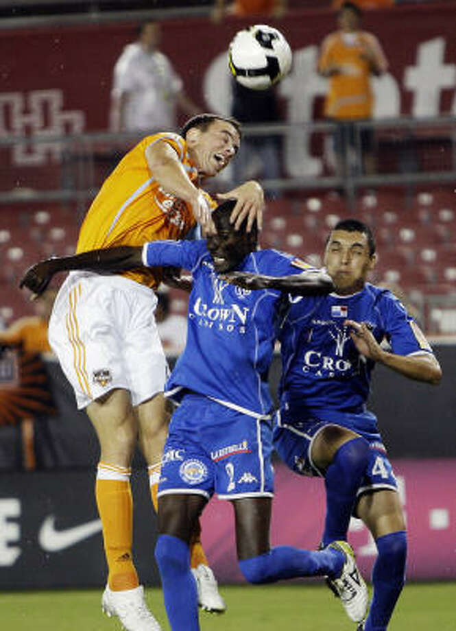 The Dynamo's Cam Weaver, left, goes up for a header over Arabe Unido's Reynaldo Lewin. Photo: Bob Levey, AP