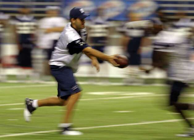 Quarterback Tony Romo is blurred from a long exposure in camera as he hands off the ball during the morning session of the Dallas Cowboys training camp at the Alamodome on Friday, Aug. 5, 2011. Kin Man Hui/kmhui@express-news.net Photo: KIN MAN HUI, -- / SAN ANTONIO EXPRESS-NEWS