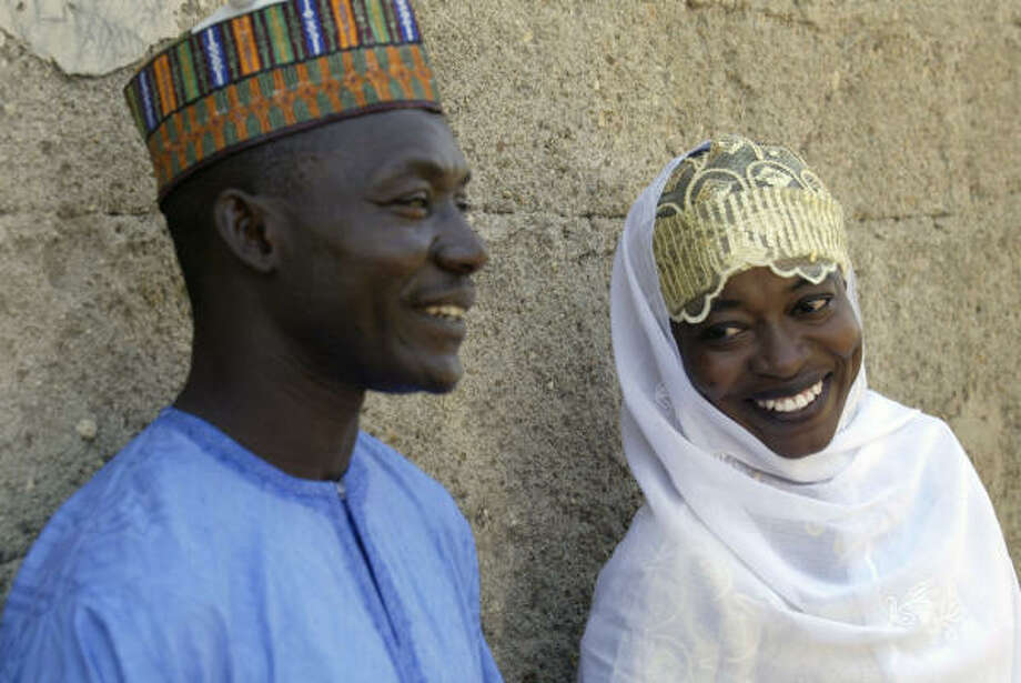Hauwa Idriss, right, and Umar Ahmed, who both have the AIDS virus, smile for photos after their wedding. Photo: SUNDAY ALAMBA, Associated Press