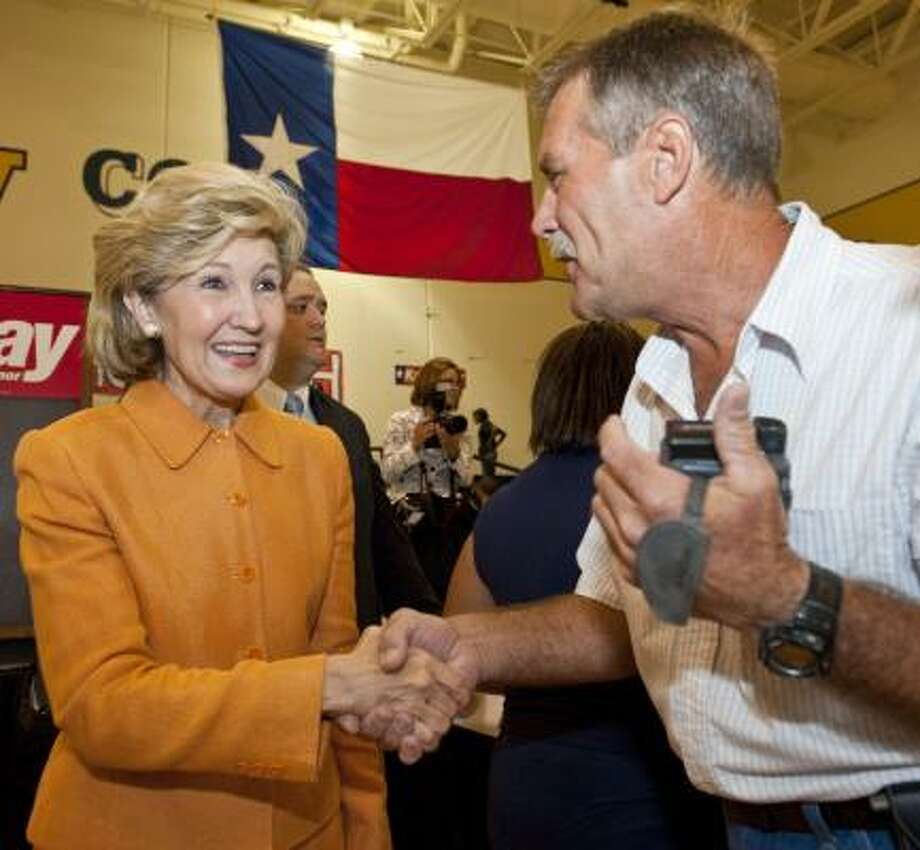 The senator greets Scott Birthuis in La Marque. Hutchison said she will propose term limits of eight years for governor. Photo: Dave Einsel, AP