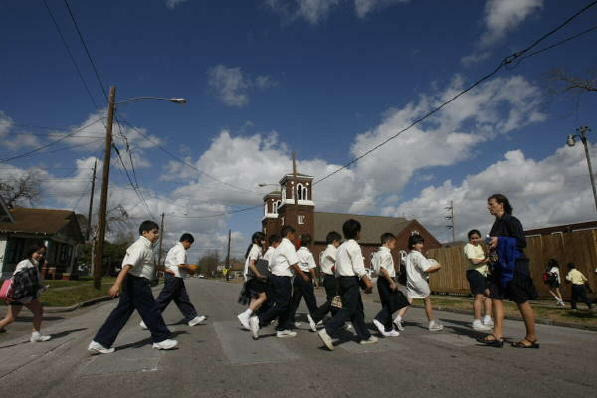 AFFECTED: Students from Holy Name Catholic School are seen crossing the street from the grass playground area back toward the school during a regular school day on Friday. Cardinal Daniel DiNardo announced the Archdiocese of Galveston-Houston will close four of its campuses, including Holy Name, after this school year. The schools are in low-income minority neighborhoods.