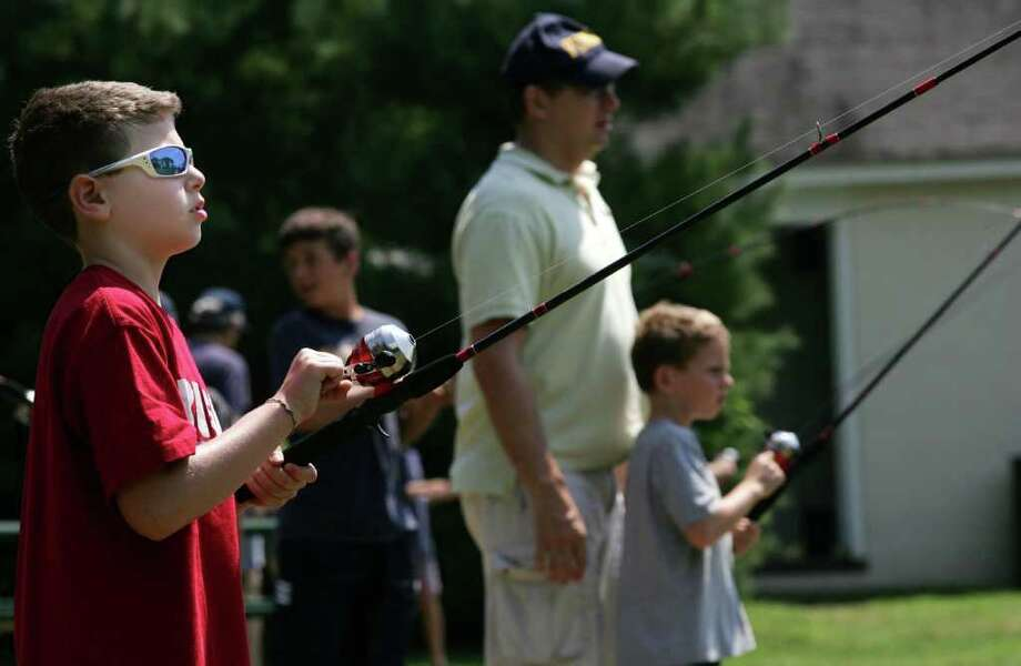 Ben Weinstein, left, practices his casting during a fishing clinic Friday, Aug 5, 2011, at Greenwich Point sponsored by the Greenwich Conservation Commission and the state Department of Energy and Environmental Protection. Photo: David Ames / Greenwich Time