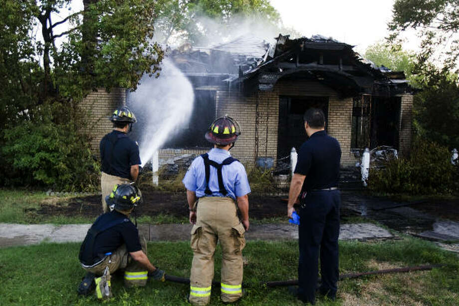 Houston firefighters works the scene of a fire at 12th Street and Herkimer. Photo: Smiley N. Pool, Houston Chronicle