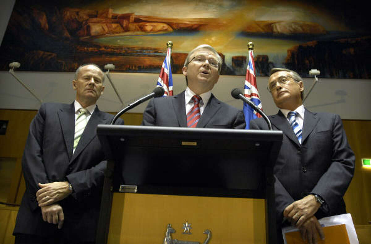 Australia's Prime Minister Kevin Rudd, center, speaks while Finance Minister Lindsay Tanner, left, and Treasurer Wayne Swan, right, look on during a press conference to announce the economic stimulus package at Parliament House, in Canberra, Australia today.