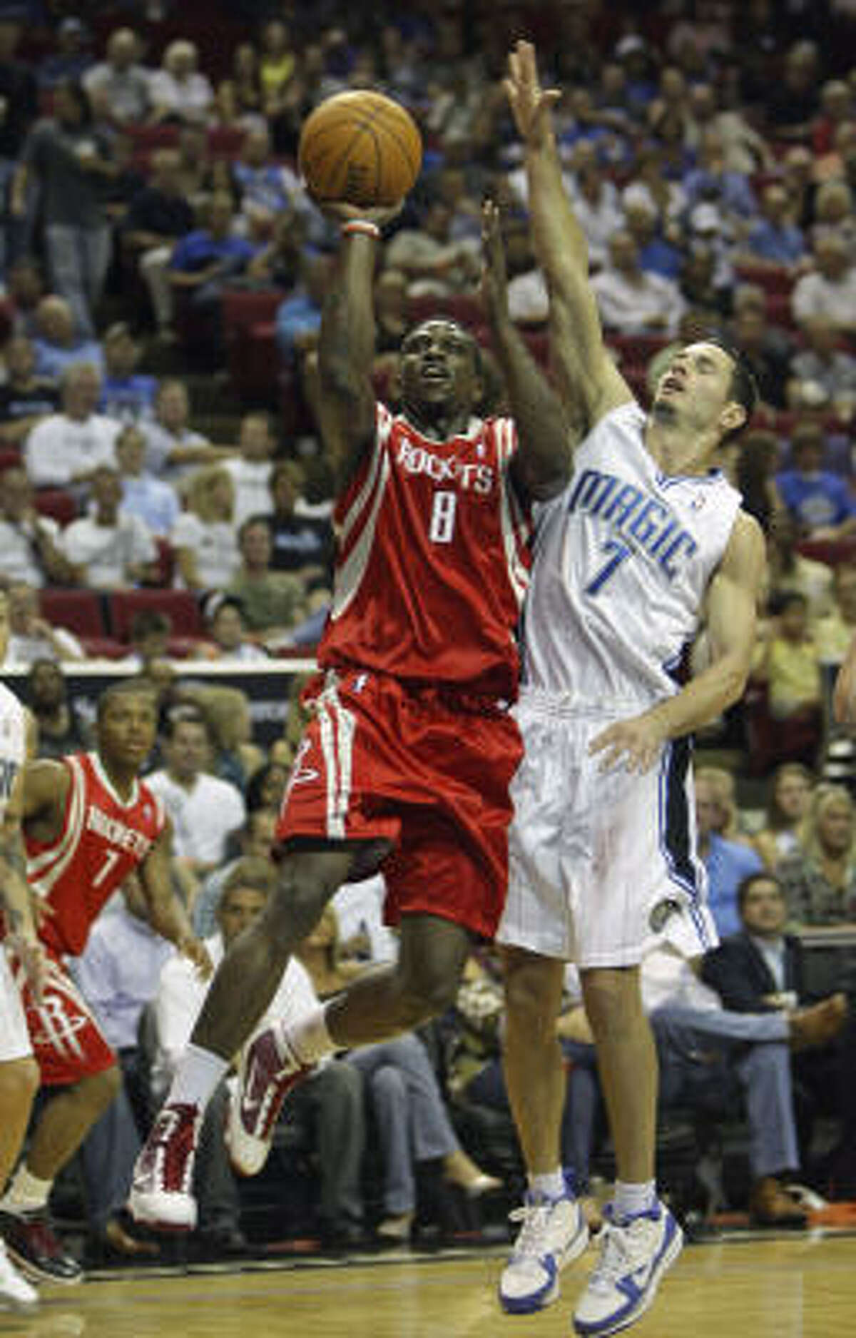 Rockets guard Jermaine Taylor gets off a shot as he is guarded by Magic guard J.J. Redick.