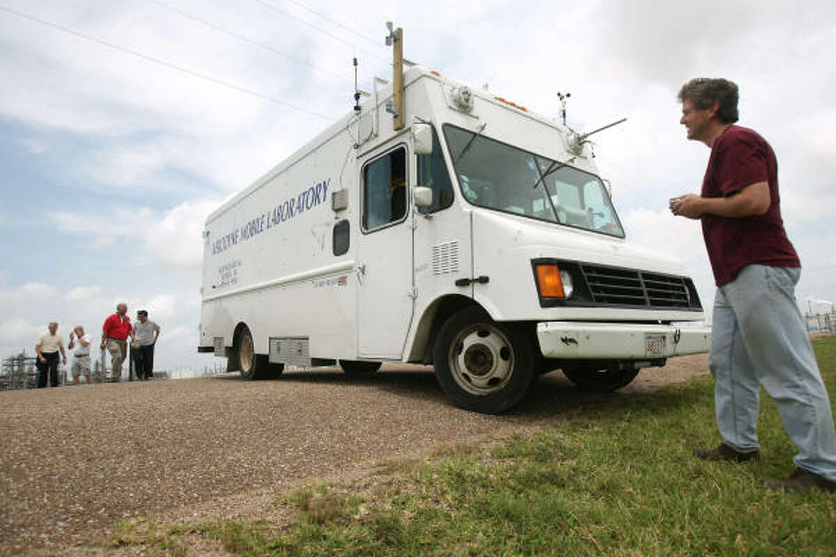 Scott Herndon, right, and other scientists collect data around an industrial complex in Texas City.
