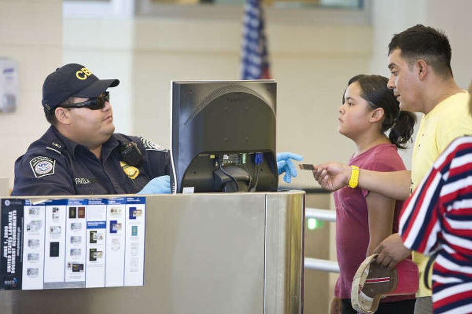 U.S. Customs and Border Protection officer Oscar Favela, left, confirms that Rubin Garcia's international traveling permit is valid last week at the port of entry in El Paso. Ports of entry have noted an upswing in impostors. Photo: Nick De La Torre, Chronicle