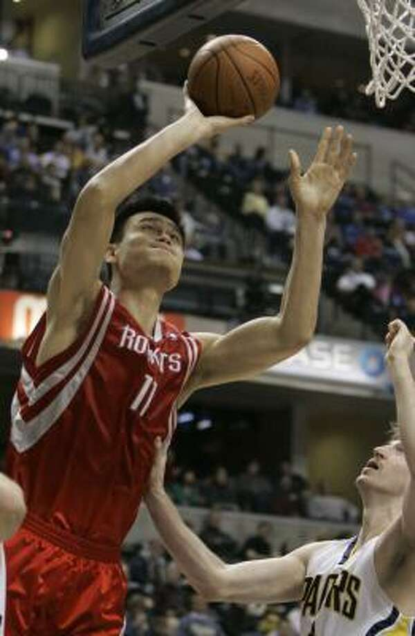Yao Ming (11) works inside against Pacers forward Troy Murphy in the second quarter. Yao finished with eight points and five rebounds in 17 minutes.  He did not play in the second half because of injury. Photo: Darron Cummings, AP