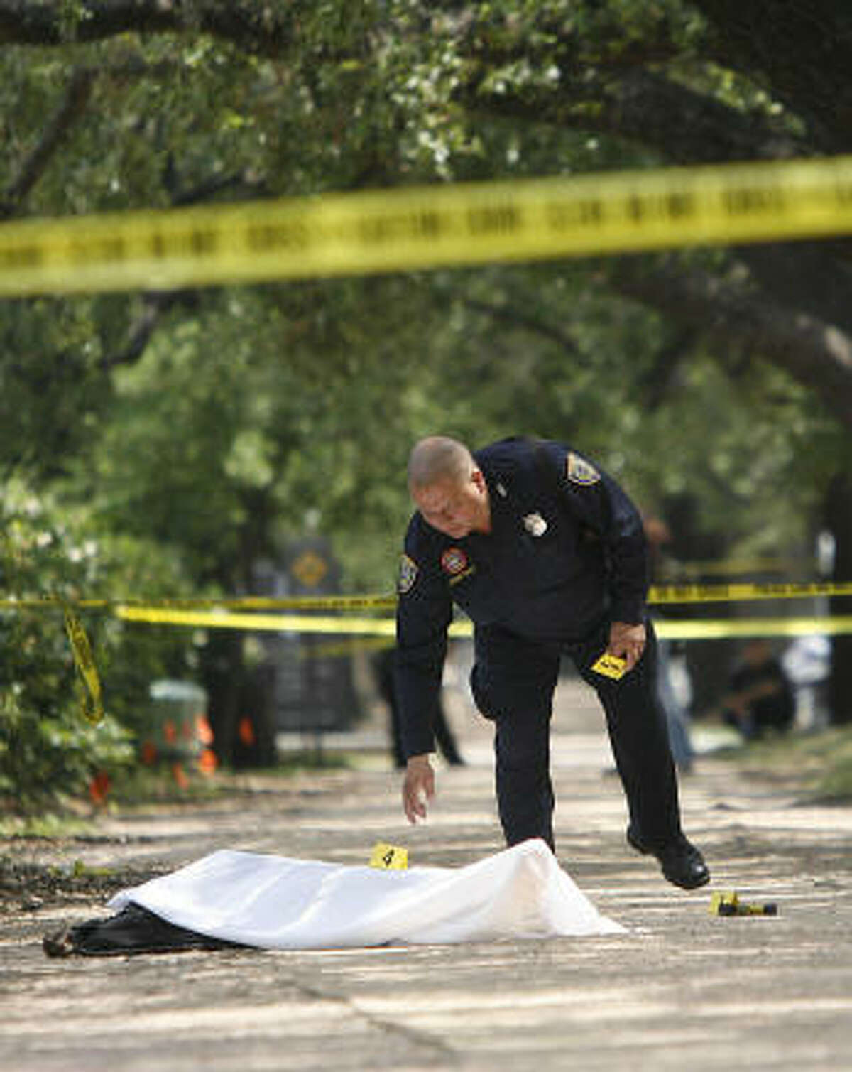 In early May, an officer examines the scene on a jogging trail near Rice University where a Metro police officer fatally shot a man resisting arrest on an assault complaint.