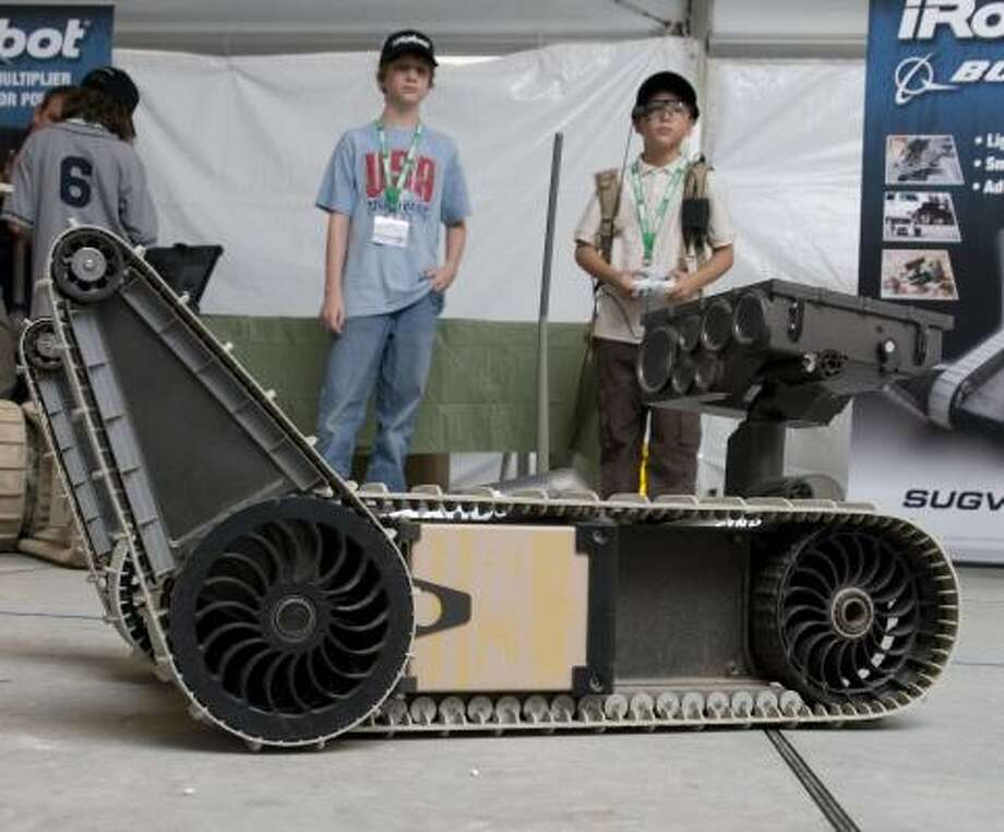"""Max Friedman, 13, left, and Justice Murray, 10, get a feel for the iRobot at Fort Hood's """"Robotics Rodeo"""" last week. Murray is handling the robot through a controller. Photo: ANDY SHARP, SAN ANTONIO EXPRESS-NEWS"""