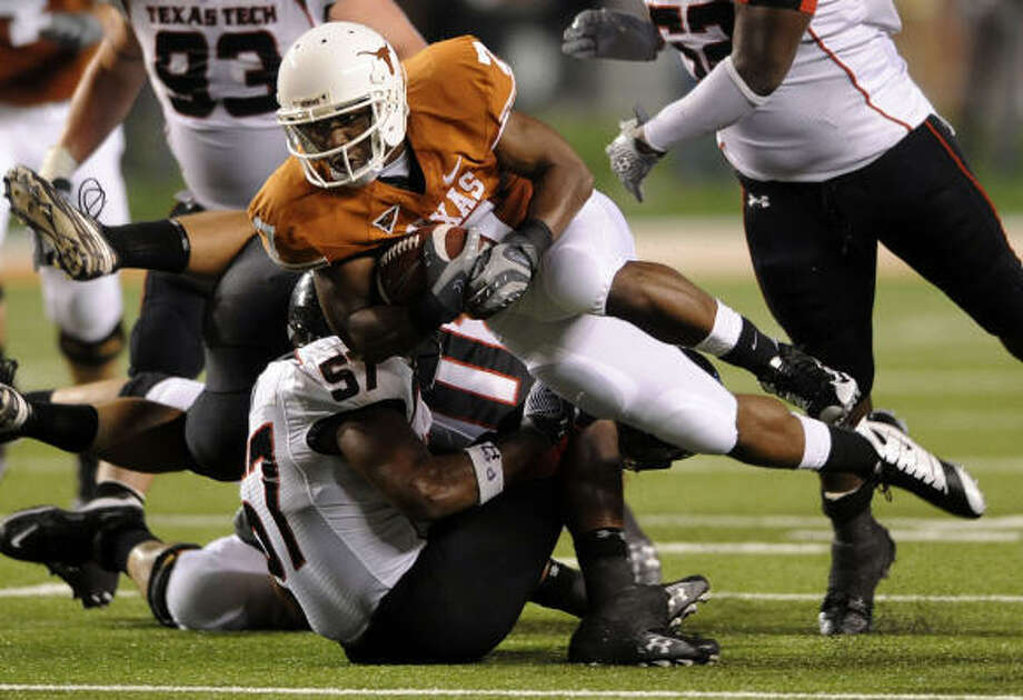 Texas' John Chiles, who rushed for 29 yards, is tripped up by Texas Tech linebacker Brian Duncan in the first half. Photo: BILLY CALZADA, SAN ANTONIO EXPRESS-NEWS