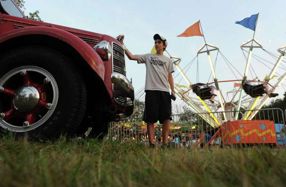Highlights from the annual Easton Fireman's Carnival in Easton, Conn. on Friday August 5, 2011. Vic Verner, 13, touches the hood ornament on the antique Easton fire truck. Photo: Christian Abraham / Connecticut Post