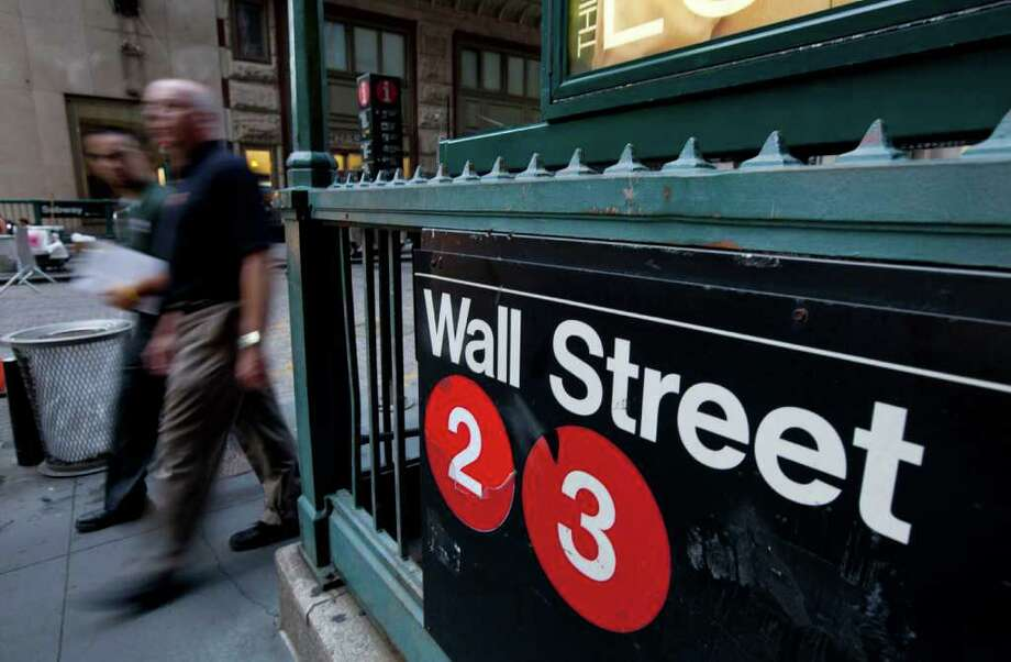 Pedestrians walk past a Wall Street sign near the New York Stock Exchange on Friday, Aug. 5, 2011 in New York. Stock market volatility, sparked by concerns about a weakening global economy, could stretch into the fall, Connecticut investment experts predict, so investors need to remain calm as they review their portfolios. (AP Photo/Jin Lee) Photo: Jin Lee, AP / AP2011