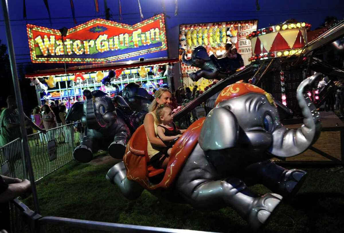 Highlights from the annual Easton Fireman's Carnival in Easton, Conn. on Friday August 5, 2011. Lilyana Connor, 2, of Stratford, enjoys a Dumbo ride with mom.