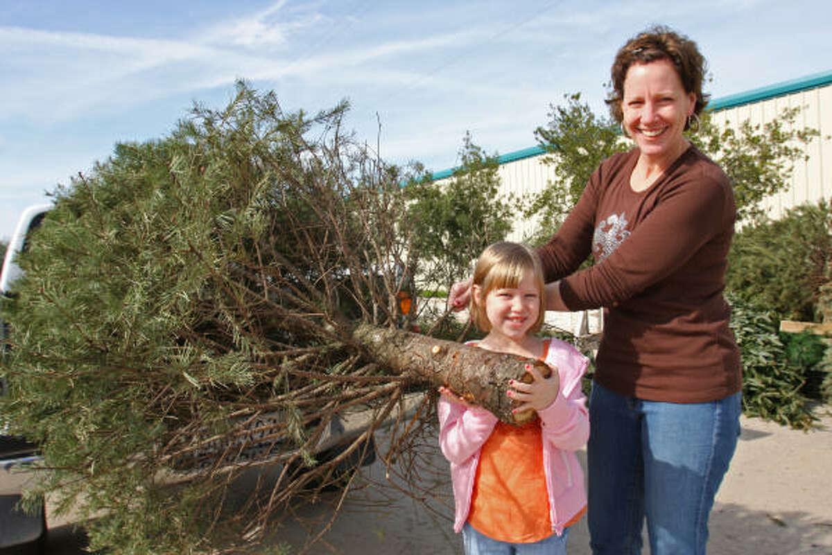 Gia Vandever of Sugar Land and her daughter, Nina, 6, recycle their Christmas tree at Eldridge Park in Sugar Land in 2008.