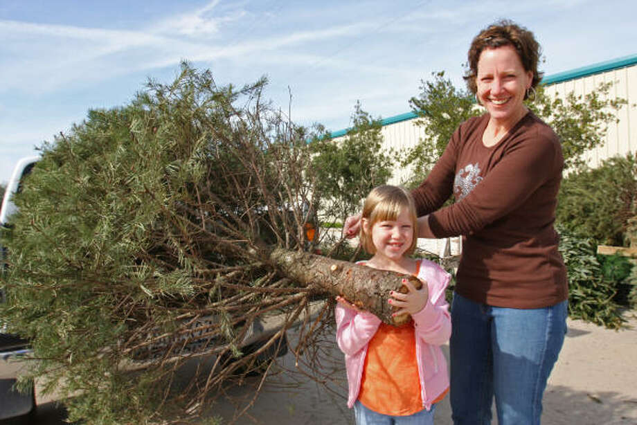 Gia Vandever of Sugar Land and her daughter, Nina, 6, recycle their Christmas tree at Eldridge Park in Sugar Land in 2008. Photo: Suzanne Rehak, For The Chronicle