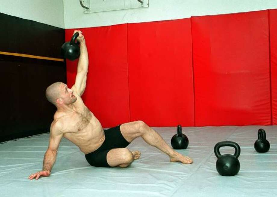 Kettlebells are easier to transfer from hand to hand. Photo: WILLIAM F. STEINMETZ, KRT