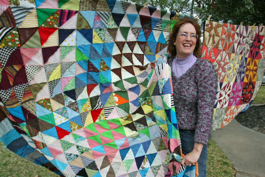 Elizabeth Proctor, owner of Limited Edition Art and Antiques, displays quilts. Photo: Suzanne Rehak, For The Chronicle