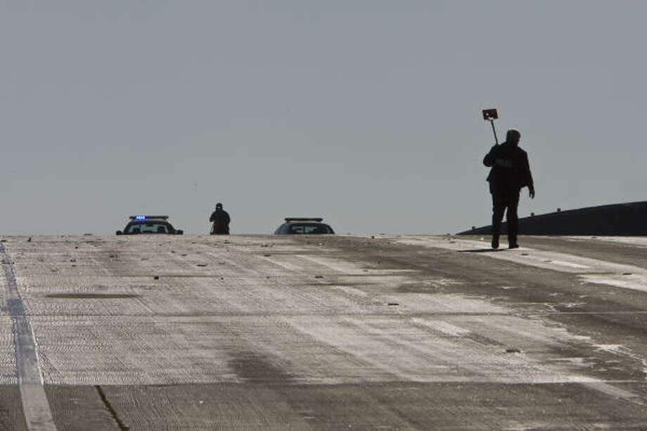 HPD officers tread carefully at the scene of a multi-car pileup on the Griggs Road overpass Saturday on I-45. The accident killed one person. Photo: James Nielsen, Chronicle