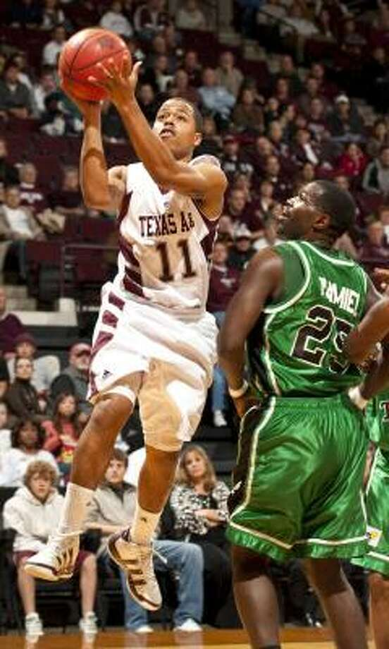 Texas A&M's B.J. Holmes drives by North Texas' Eric Tramiel during the first half. Photo: Dave Einsel, AP