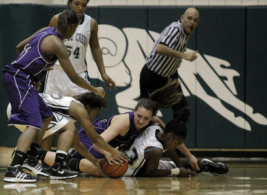 Morton Ranch's Laura Anderson, center, fights for a loose ball during the Lady Mavericks matchup with Mayde Creek on Tuesday. Photo: Todd Spoth, For The Chronicle