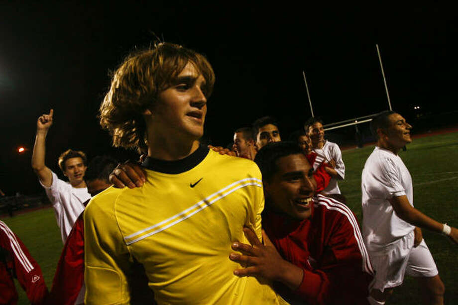 Katy High School soccer goalkeeper John Huttenhoff is congratulated by teammates after leading his team to a victory against Elsik. Huttenhoff played despite being ill before the game. Photo: Michael Paulsen, Chronicle