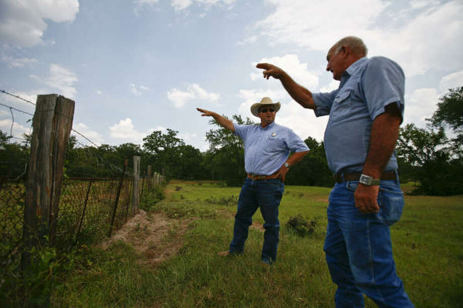 Iola rancher Jerry Norman, right, shows Brent Mast, a ranger who tracks stolen cattle, where his bull disappeared last month. Photo: Michael Paulsen, Chronicle