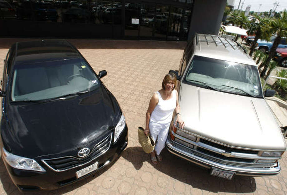 "Maria Lacy, an elementary school teacher who lives in the Upper Kirby area, is all smiles after trading in her Chevy Tahoe, right, for a Toyota Camry through the new ""cash for clunkers"" program on Tuesday. Photo: Julio Cortez, Chronicle"