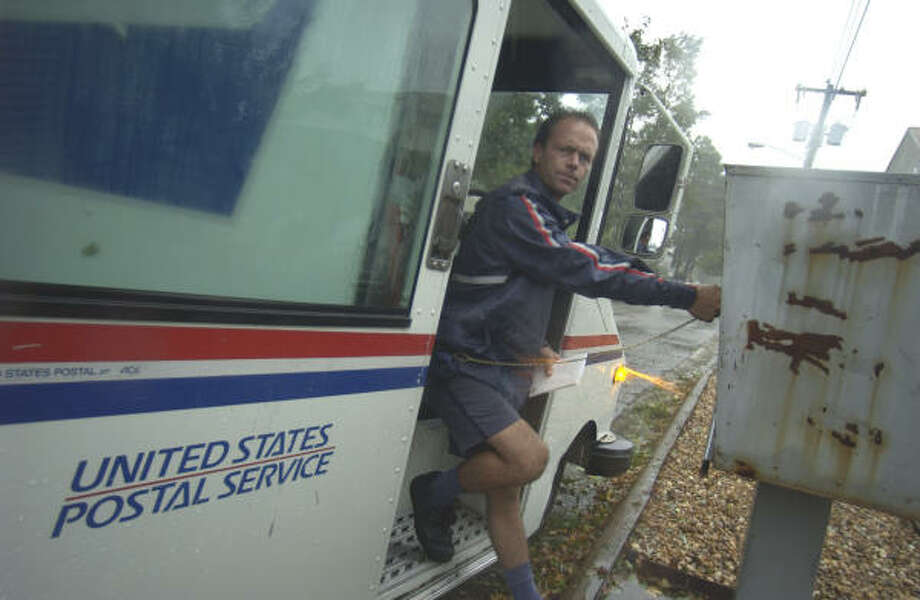 In this Sept. 18, 2003 photo, Virginia Beach postman Paul Martin delivers mail in Virginia Beach, Va. Massive deficits facing the post office could force the agency to cut out one day of mail delivery per week. Photo: STEVE HELBER, AP