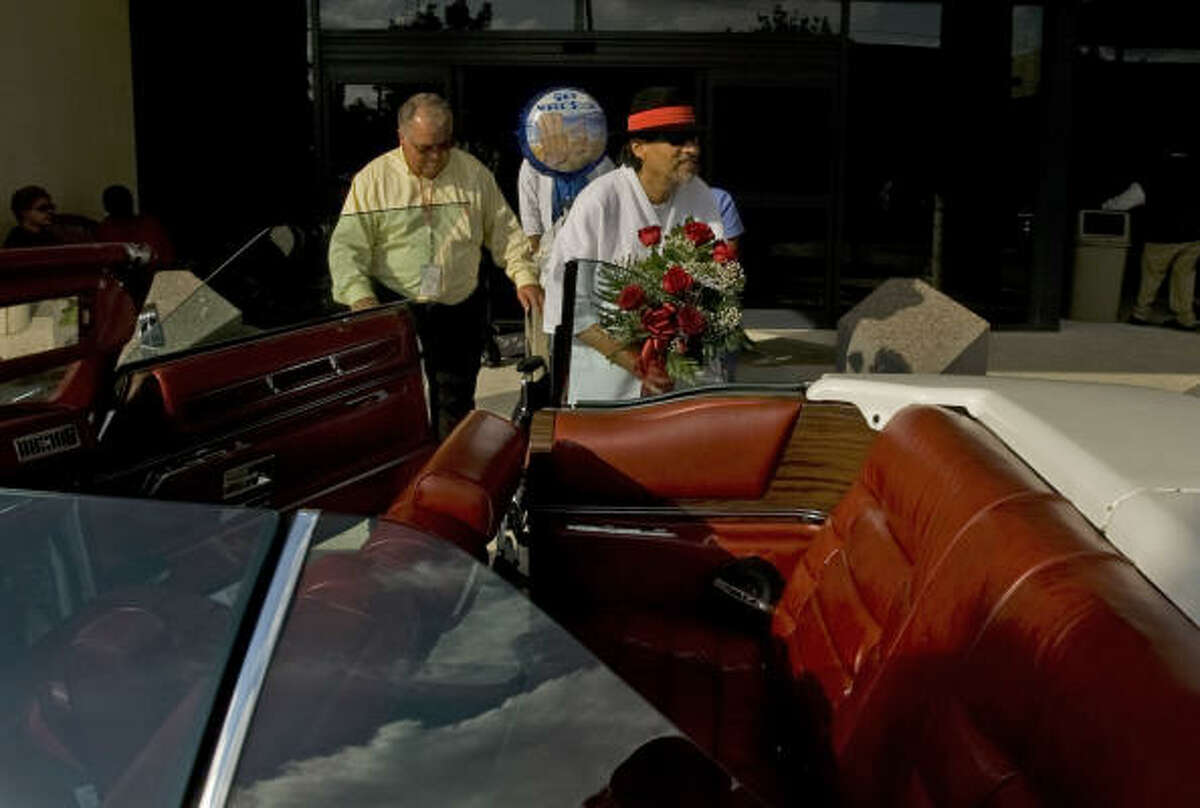 Pancho Claus, aka Richard Reyes, right, is helped into his low-riding Cadillac by friend Hector Garcia after Reyes left Memorial Hermann Northwest Hospital, where he was treated for a heart attack he suffered last Monday.