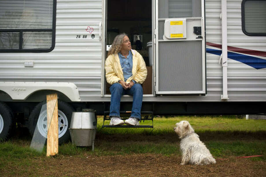"Ann Harrington, with her miniature schnauzer Emily, says living in a cramped FEMA trailer near her damaged home in Galveston ""wears on you."" Photo: Todd Spoth, For The Chronicle"