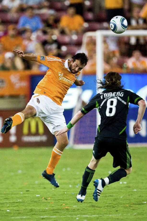 Houston Dynamo midfielder Adam Moffat (16) heads the ball against Houston Dynamo defender Kofi Sarkodie (8) during the second half of the Major League Soccer game between the Houston Dynamo and Seattle Sounders at Robertson Stadium on Saturday, July 30, 2011 in Houston. The Dynamo beat the Sounders 3-1. ( Patrick T. Fallon / Houston Chronicle ) Photo: Patrick T Fallon, Intern / © 2011 Houston Chronicle