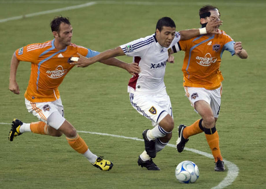 Brad Davis, left, and Richard Mulrooney, right, battle Real Salt Lake's Javier Morales for possession in the first half. Photo: James Nielsen, Chronicle