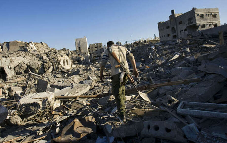 A Palestinian Hamas member walks through the debris of a destroyed Hamas security compound, which includes the central jail, in Gaza City, Sunday. Photo: Bernat Armangue, AP