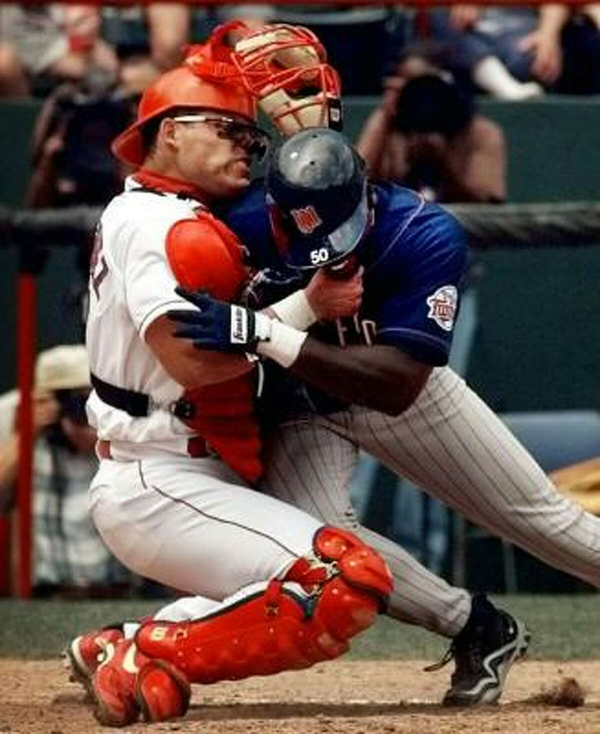 1998: Rodriguez shows his durability, shaking off a collision with the Twins' Matt Lawton, left, during a four-year run with Texas in which he played at least 144 games each season.