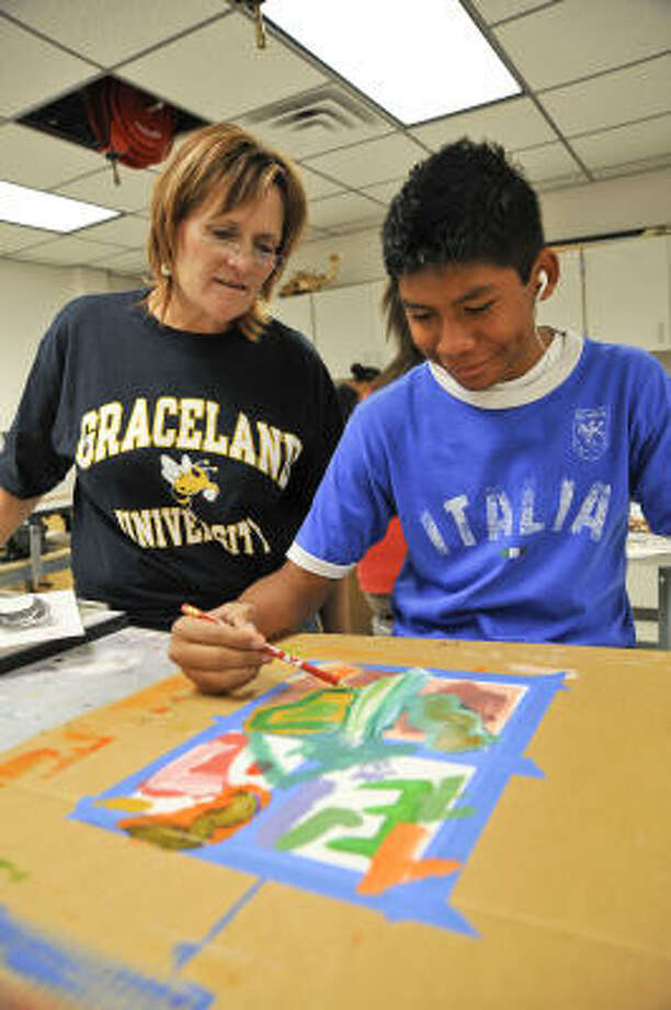 A HELPFUL EYE: Stephanie McClain, a teacher at Pasadena Memorial High, helps Eden Galvan, a Dobie High student, as he works on an art project during one of the Gear Up summer camp sessions at San Jacinto College Central. Photo: Rob Vanya, For The Chronicle