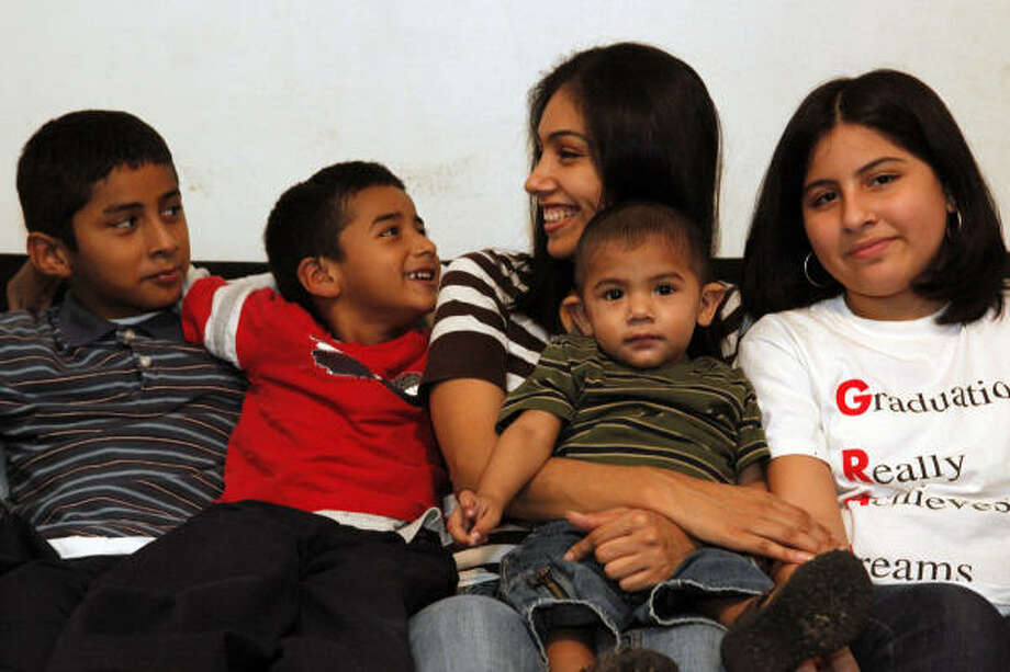 Amanda Reconco says she and her husband are focusing on what's most important at Christmas: family. From left, her children are Jim Reconco, 9; Andrew Reconco, 5; Manuel G. Ybarra Jr., 14 months; and Alexis Hernandez, 11. Photo: TODD SPOTH, Chronicle