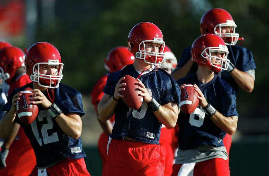 The group of Houston QB's (l-r) Cotton Turner, 12; Crawford, 13; David Piland, 8; and Drew Hollingshead, 2, line up to throw at the first practice for the University of Houston football team, at their practice field on campus, Friday, Aug. 5, 2011,in Houston. ( Karen Warren / Houston Chronicle ) Photo: Karen Warren, Staff / © 2011 Houston Chronicle