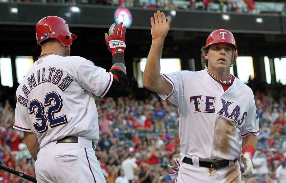 Josh Hamilton and Ian Kinsler celebrate during the Texas Rangers' 8-7, 11-inning victory over the Cleveland Indians on Friday. Photo: Ronald Martinez, Ronald Martinez/Getty Images / 2011 Getty Images