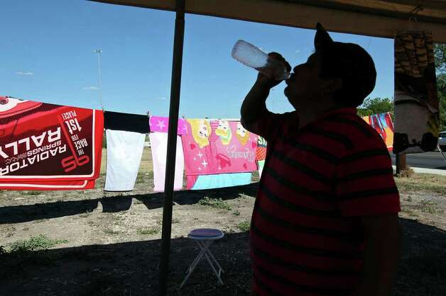 "Jose Perez takes a drink of water as he sells blankets and towels along Culebra Road, Wednesday, Aug. 3, 2011. Although selling blankets in this heat wave sound like a far fetch idea, Perez says he counts on the characters on the blankets appealing to children. ""I make enough to eat,"" he said. Photo: JERRY LARA, Express-News / SAN ANTONIO EXPRESS-NEWS"