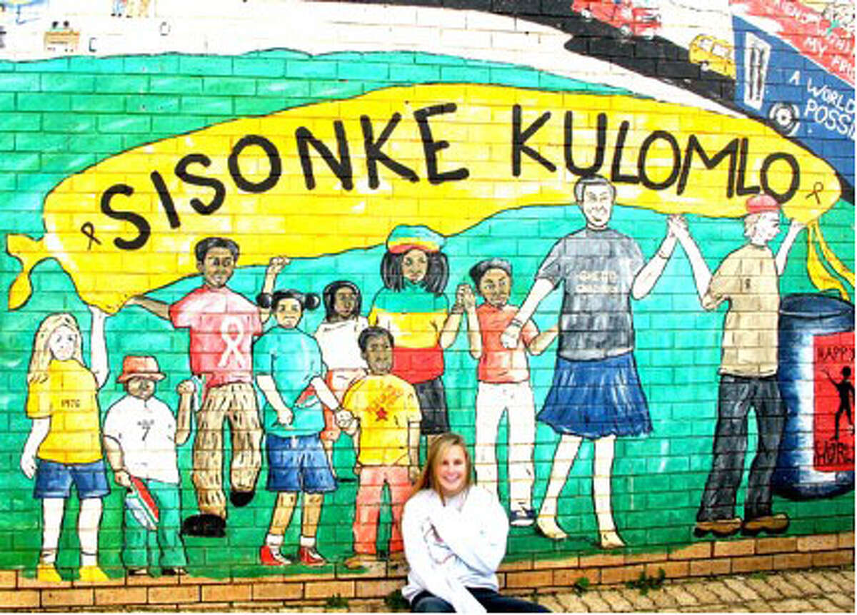Madeleine Lippey, 15, a Greenwich resident and sophomore at Philips Academy in Andover, Mass., traveled to Port Elizabeth, South Africa, in July to film a promotional video for the Ubuntu Education Fund that inspired her to create the Do Write Campaign, a global online literary magazine for teens. Pictured, she sits in front of a sign that reads