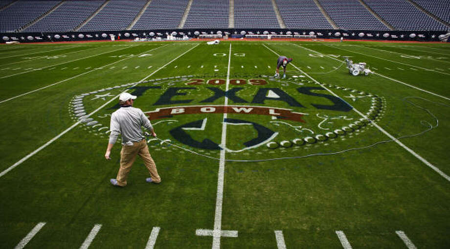 Derek Hutchinson (left) and E.J. Besold work to paint the 2009 Texas Bowl logo. Photo: Michael Paulsen, Chronicle