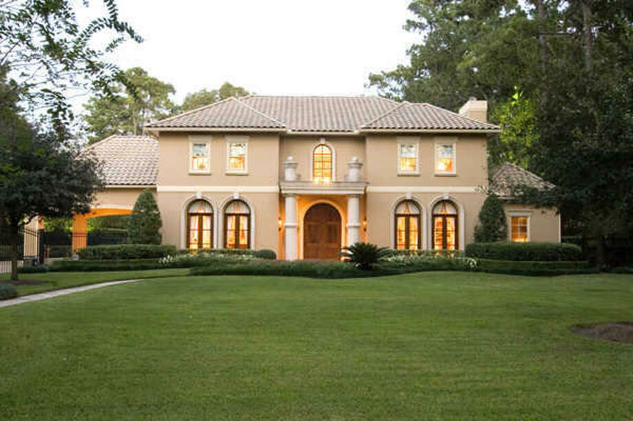Italian exterior with tile roof, arched windows and 2 car gated porte-cochere. Photo: Martha Turner Properties
