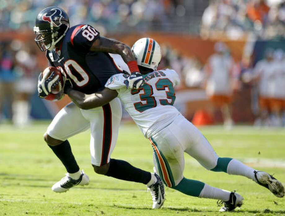 Texans wide receiver Andre Johnson is hit by Dolphins cornerback Nate Jones after making a reception during the second quarter of Sunday's 27-20 victory over the Miami Dolphins. Johnson had five catches for 71 yards and a touchdown for his second consecutive 1,500-yard season. Photo: Brett Coomer, Chronicle