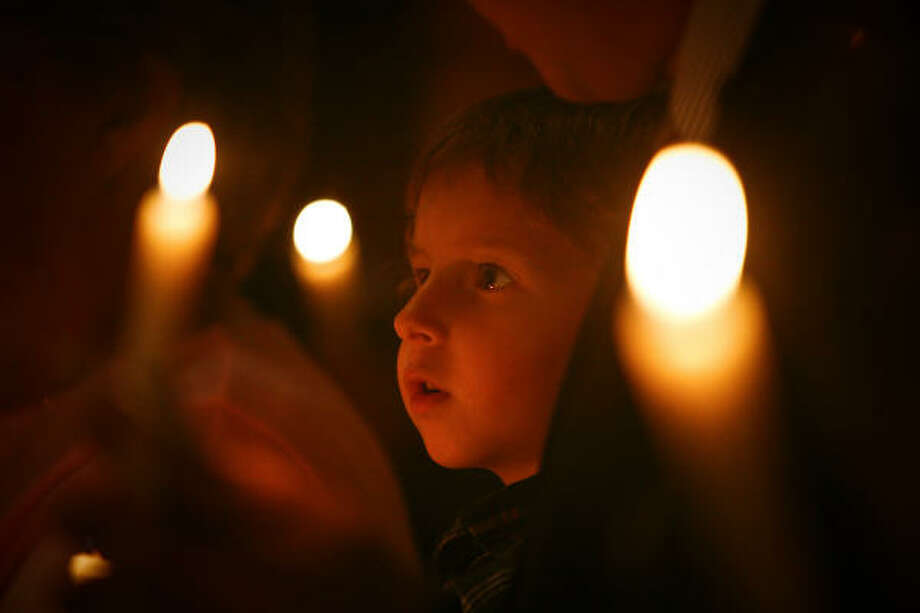 Sean Williams, 5, join others celebrating Jesus' birth at a candlelight service at First United Methodist Church in Missouri City Christmas Eve. Photo: Michael Paulsen, Chronicle