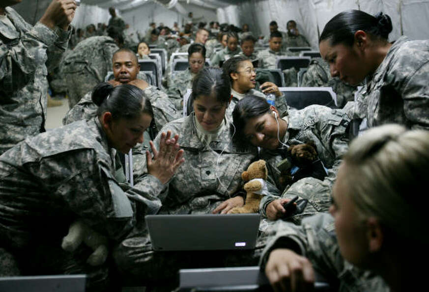 Spc. Jacqueline Castro, 20, of El Paso, high-fives Spc. Savanna Garcia, 23, during a game of Scrabbl