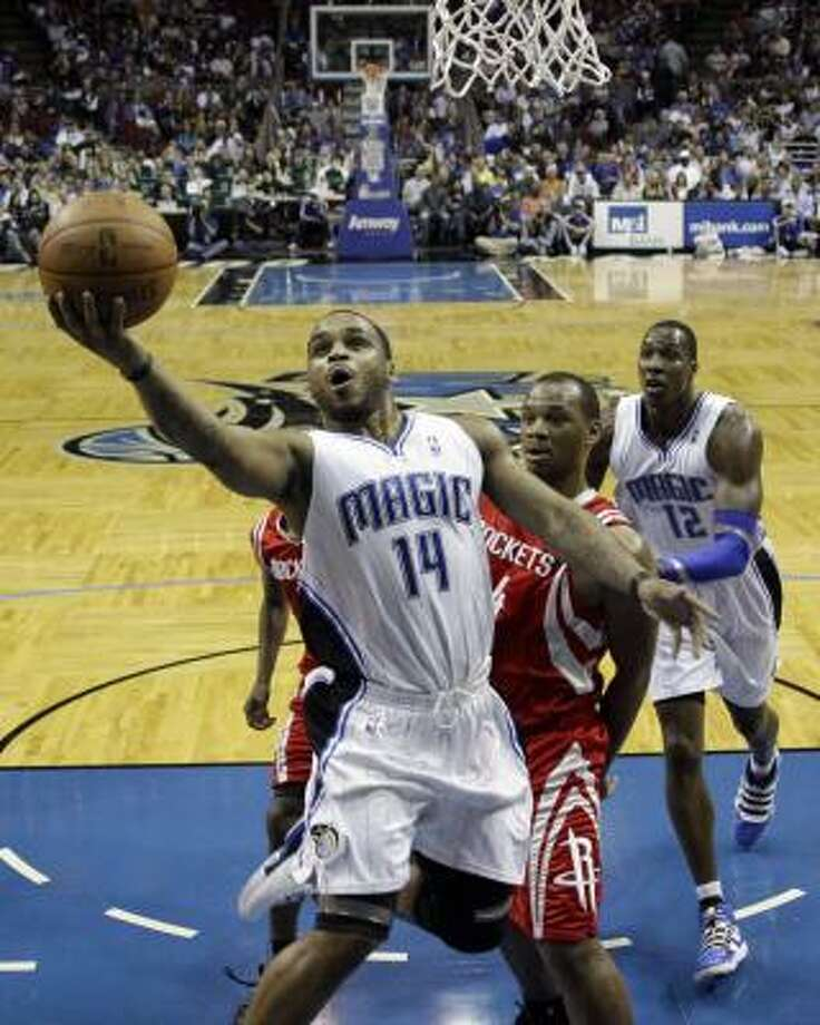 Dec. 23: Magic 102, Rockets 87Magic guard Jameer Nelson (14) takes a shot in front of Rockets forward Carl Landry during the first half. Photo: John Raoux, AP